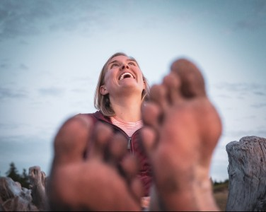 Erin Augustine, smiling with dirty toes in the foreground. Photo taken by Nick Irwin of Nick Irwin Images. Find him at www.nickirwinimages.com and @irwin.nick on Instagram