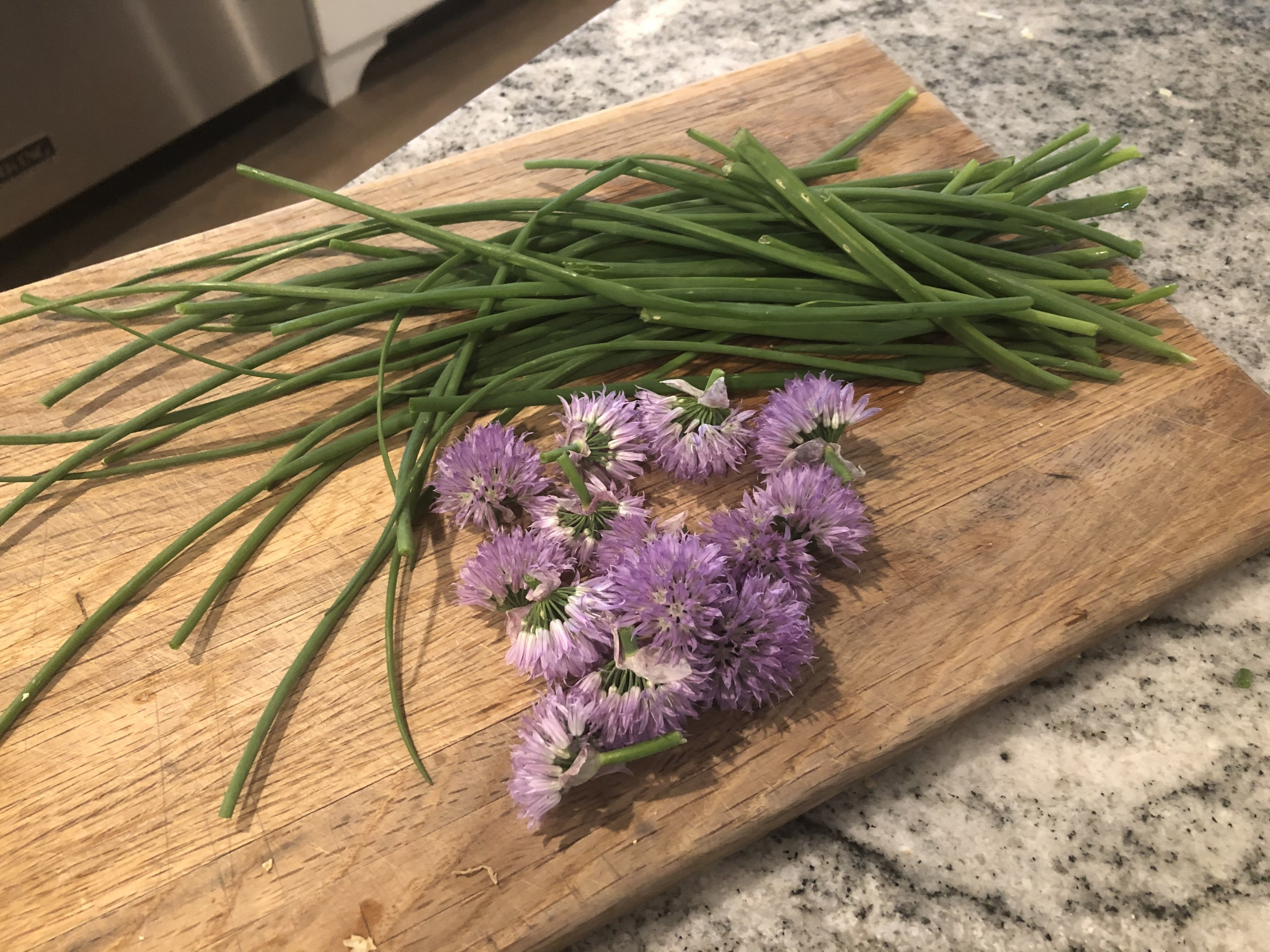 Harvested chives on my cutting board, with blossoms removed